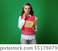 student woman with yellow book on chalkboard green background 55176079