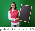 student showing black chalkboard isolated on green background 55176124