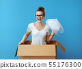 woman in a cardboard box with air bubble film packaging material 55176300