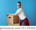 young woman in white t-shirt near cardboard boxes on blue 55176302