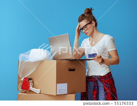woman near cardboard box with laptop and credit card on blue 55176333