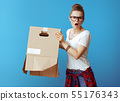 woman shakes out something from old cardboard box on blue 55176343