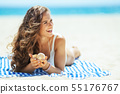 woman with seashell laying on a striped towel and looking aside 55176767