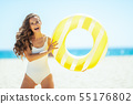 smiling woman on ocean coast holding yellow inflatable lifebuoy 55176802