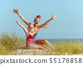 happy modern mother and child in beachwear on beach rejoicing 55176858
