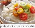 Somen above the wood board in a glass transparent bowl with mini tomatoes 55179564