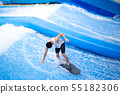 Unidentified man playing surfboard indoor extreme sport. 55182306