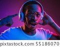 Young african-american man's listening to music in neon light 55186070