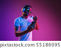 Young african-american man's listening to music in neon light 55186095