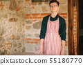 Young male artist in aprong and glasses stand in front of brick wall 55186770