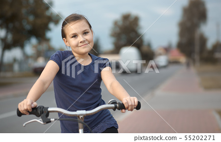Cute girl is sitting on bicycle 55202271