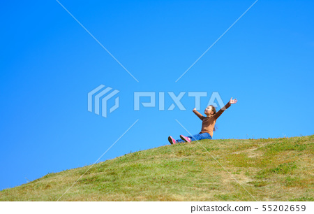 Portrait of a little girl sitting on green grass 55202659