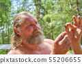 Bearded old man holding a large insect in his 55206655
