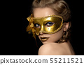 Young beautiful woman wearing golden party mask 55211521
