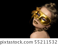 Young beautiful woman wearing golden party mask 55211532