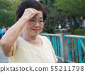 The elderly asian woman wore a glasses. she was 55211798
