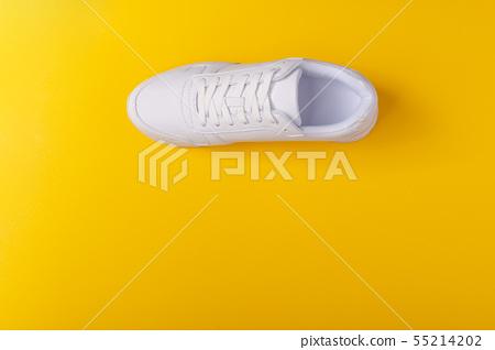 A studio shot of white running shoe on yellow background. Flat lay. 55214202