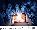 Scared girl and boy reading book in bed 55229305