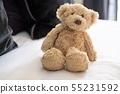 하얀 침대에 앉아 귀여운 테디 베어 (곰 인형) 55231592
