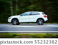white luxury suv car goes fast through the forest 55232362