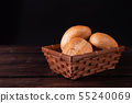 Buns in bread basket on a wooden background, low 55240069
