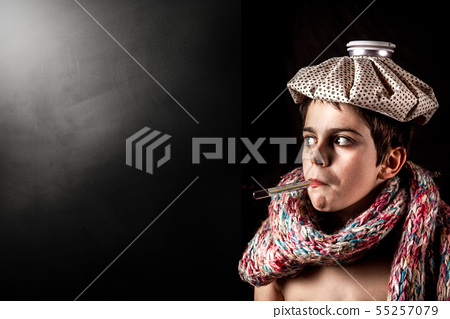 sick kid with thermometer and ice pack 55257079