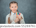European first grader's hands are full of colorful pencils. 55269761