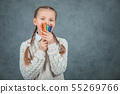 Cute schoolgirl is watching through the colorful pencils. 55269766