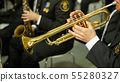 The trumpeter is playing on a silver trumpet. Trumpet players. 55280327