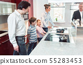 Expert explaining new kitchen to family looking for one 55283453