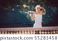 Woman forcefully playing tennis 55283458