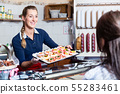 Sales woman in butcher shop offering finger food 55283461