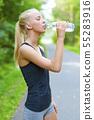 Female runner drinking water after running 55283916