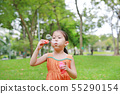 Asian little girl blowing soap bubbles in green 55290154