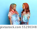 girls with satisfied expressions standing isolated over blue background 55290348