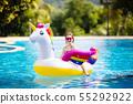Child on unicorn float in swimming pool. Kids swim 55292922