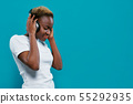 Pretty african girl listening music with headphones. 55292935