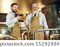 Cheerful brewers holding glasses with light and dark beer. 55292994