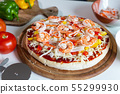 seafood pizza with shrimp on a table. 55299930
