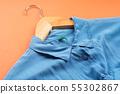 Blue woman's shirt on hanger on orange 55302867