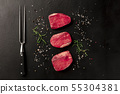 Raw fillet or sirloin beef steaks with salt, pepper and rosemary, with a carving fork 55304381