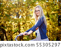 Blond long-haired attractive girl on pink lady bicycle in sunny autumn park on trees background. 55305297