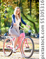 Blond long-haired attractive girl on pink lady bicycle in sunny autumn park on trees background. 55305316