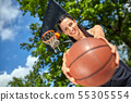 Beautiful, sporty latin girl with a basketball under the ring on a street basketball court. Sport 55305554