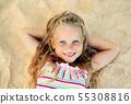 Pretty little blonde girl portrait lying on sandy beach during summer vacation 55308816