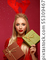Beautiful blonde girl in a New Year's image with boxes of gifts in hands and deer horns on her head 55309467
