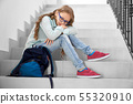 Pretty, sad schoolgirl sitting on staircase in school. 55320910
