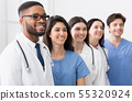 Team of doctors and interns standing in hospital in row 55320924