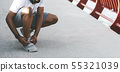 Black sporty man checking on his shoelaces 55321039