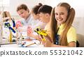 Friendly schoolgirl holding robot model in classroom 55321042